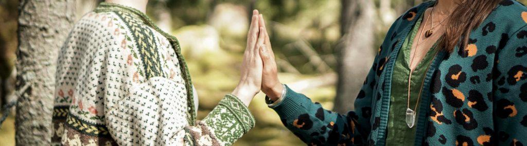 Kahden henkilön ylävartalot, henkilöt seisovat ja heillä on kädet vastakkain